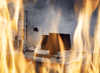 A small business office with two desks with computer workstations on fire
